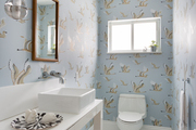 A half bathroom with light blue wallpaper.