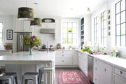 A kitchen with marble countertops, casement windows, and metal stools