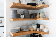 Wooden shelves with ceramic kitchen pieces sitting on top.