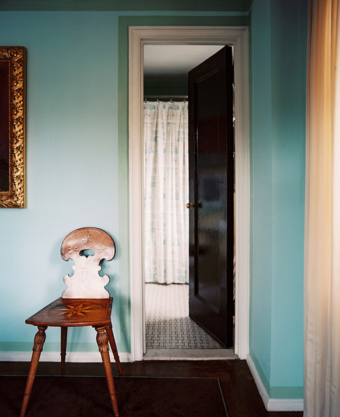 Hallway Chair - An antique wooden chair and a gold-frame mirror against blue walls