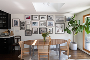 A dining room complimented with picture frame walls, black kitchen cabinets, and a corner plant.