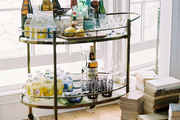 A brass bar cart of spirits, mixers, and glassware