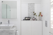 This is an all-white bathroom with some gray tile.