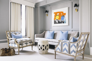 A seating area in a gray-walled master bedroom with periwinkle-blue-and-white upholstery fabric on twin armchairs