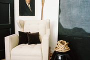 A tufted white wingback chair on a striped rug