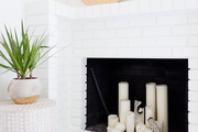 A white fireplace with white candles.