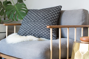 A gray chair with a gray pillow next to a gold side table.