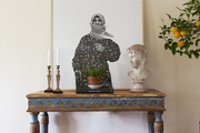 An eclectic vignette of candlesticks and sculpture atop a painted console table