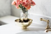 A detail of a gold bowl in a bathroom with white marble.