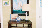 A white lamp and children's artwork surrounding a nautical painting