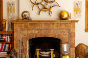 A Batchelder fireplace flanked by Italian Murano glass sconces