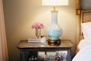 A mirrored bedside table topped with a blue lamp