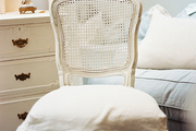 A white cane-back chair with a ruffled slipcovered seat