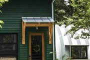 A green barn is repurposed into a retail space.