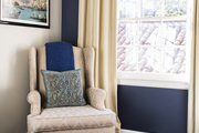 A wingback chair against a navy wall