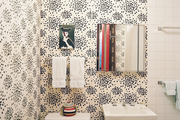 Black-and-white-patterned wallpaper and square white tile in a bathroom