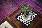 A coffee table on top of a bright purple rug