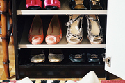 Shoes organized on shelves beside a patterned rug