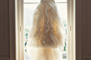 A wedding dress hung in front of french doors