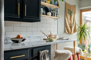 Globally inspired kitchen space with subway tile and red counter stools
