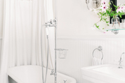 A white bathroom with a white clawfoot tub.