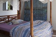A canopy bed draped in netting and dressed in graphic linens at the Spanish home of artist Pepa Poch.