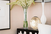 A black-and-white end table with a white lamp and a vase of flowers