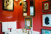 A white pedestal sink and framed art in a bathroom with red walls and a pair of sconces