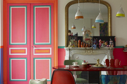Brightly painted double doors in a quirky Paris dining room with mismatched chairs around the table