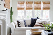 A white living area complimented with plants and patterns.