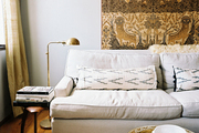 A tapestry hung behind a white couch with a brass floor lamp
