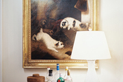 Bar essentials on a silver tray below an antique painting