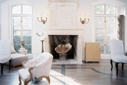 Upholstered furniture and a pair of shaded sconces in a white-walled living space