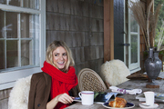 Designer Michelle Smith at the rustic dining table on her shingled Sag Harbor porch