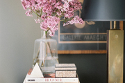 A brass lamp and a stack of books on a wood surface