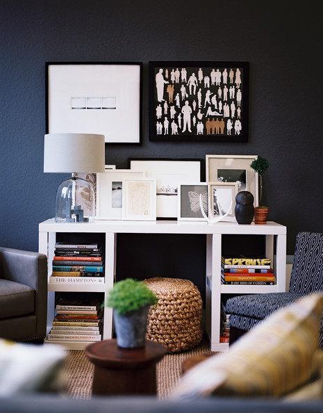Living Room - Framed art and a glass lamp atop a white desk surrounded by upholstered seating