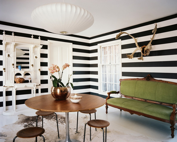 Living Room - Horizontally striped walls paired with a green antique settee and a round tulip-style table