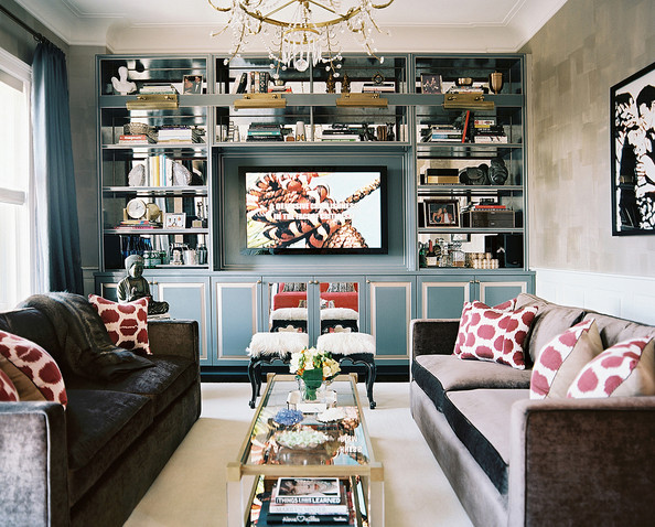 Living Room - A living space with matching gray couches and blue built-in bookshelves backed by mirror