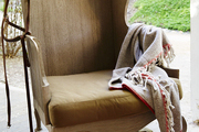 An equestrian tack room with a wingback chair and throw blanket