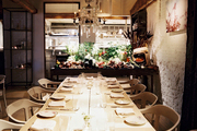A communal dining table and an open kitchen at ABC Kitchen