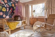 eclectic pink girl's nursery with rattan furniture, mural wall, and vintage rocker
