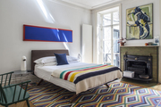 A midcentury-inspired bed topped with a striped wool blanket