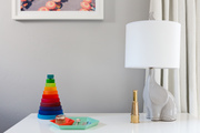 Contrasting decor and elephant-shaped lamp atop white dresser.