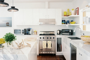 Marble countertops and white cabinetry in a bright kitchen