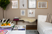 Group of framed artwork above small bench with fur padding.