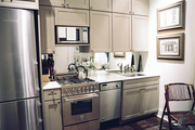 Gray cabinets and marble countertops in an open kitchen