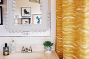A yellow shower curtain and a white mirror in a bathroom