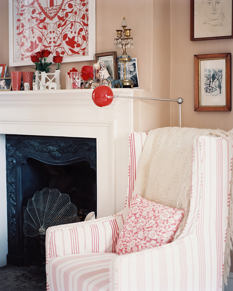 Mantel - A striped armchair beside a red floor lamp and a white mantel