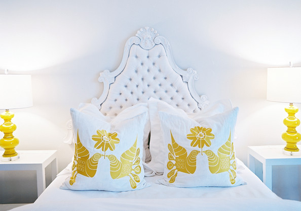 Mexican - A tufted white headboard between a pair of yellow lamps