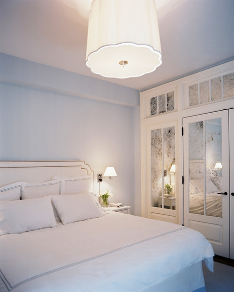 Mirrored Closet Doors - A scalloped light fixture paired with mirrored closets and a white bed and bedding